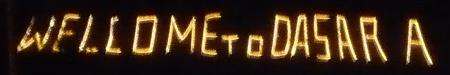 Eine Leuchtschrift, die am Rand der Stadt auf einem Huegel steht und von Englisch nach Kanada wechselt